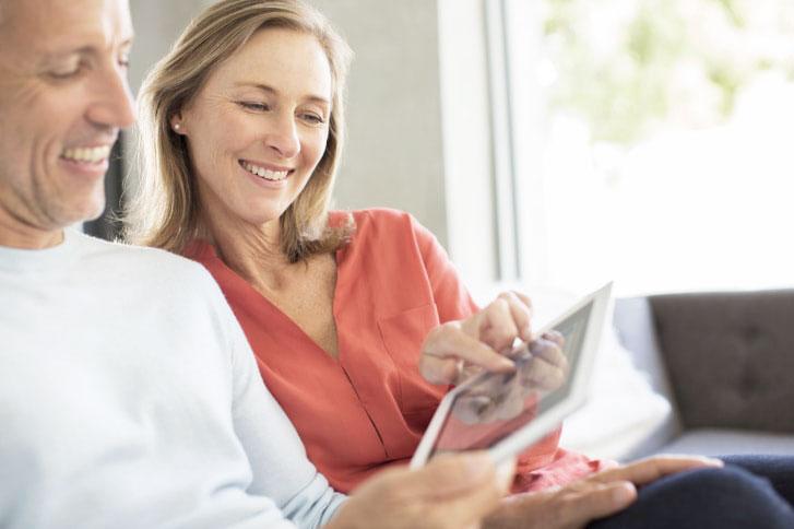Couple sitting on sofa using digital tablet