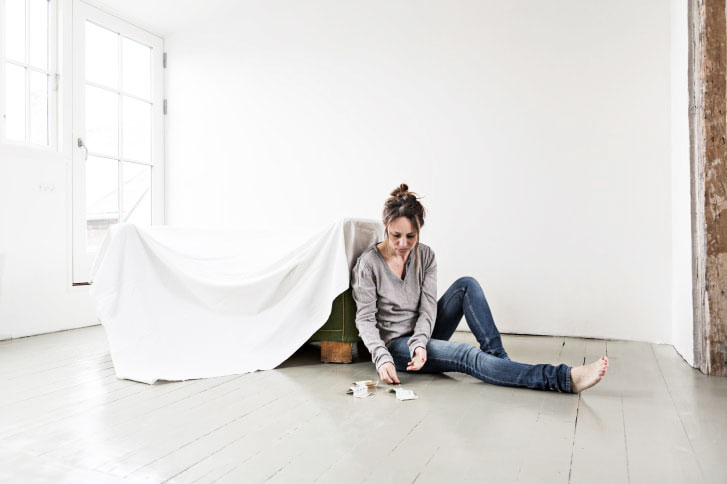 Mature woman sitting on floor in empty house, counting money