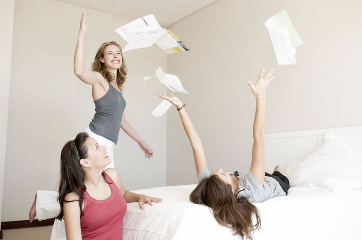 Three flatmates throw bills in the air