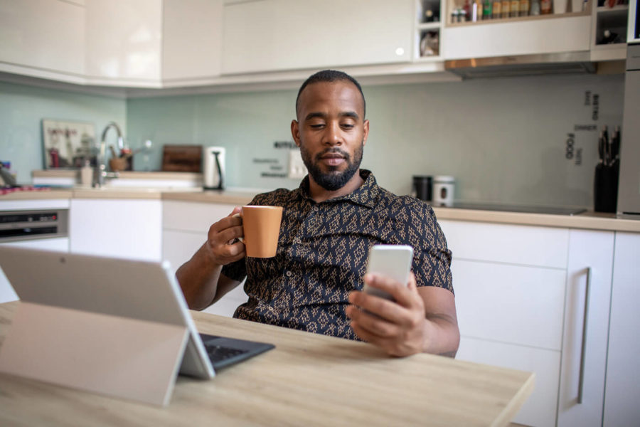 Latin Men Is Shopping Online And Drinking Coffee