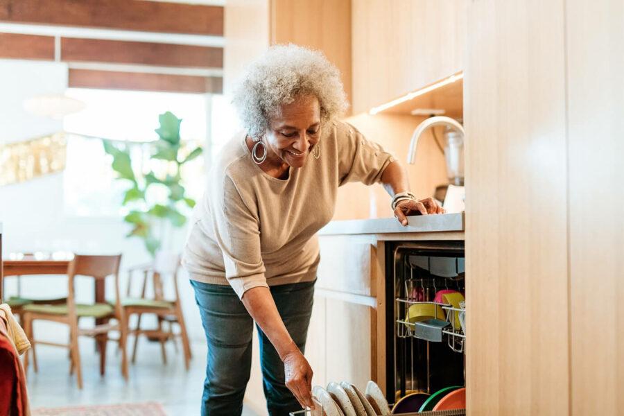 Smiling senior woman keeping plates in dishwasher