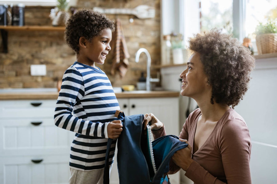 Single black mother packing her small son for school.
