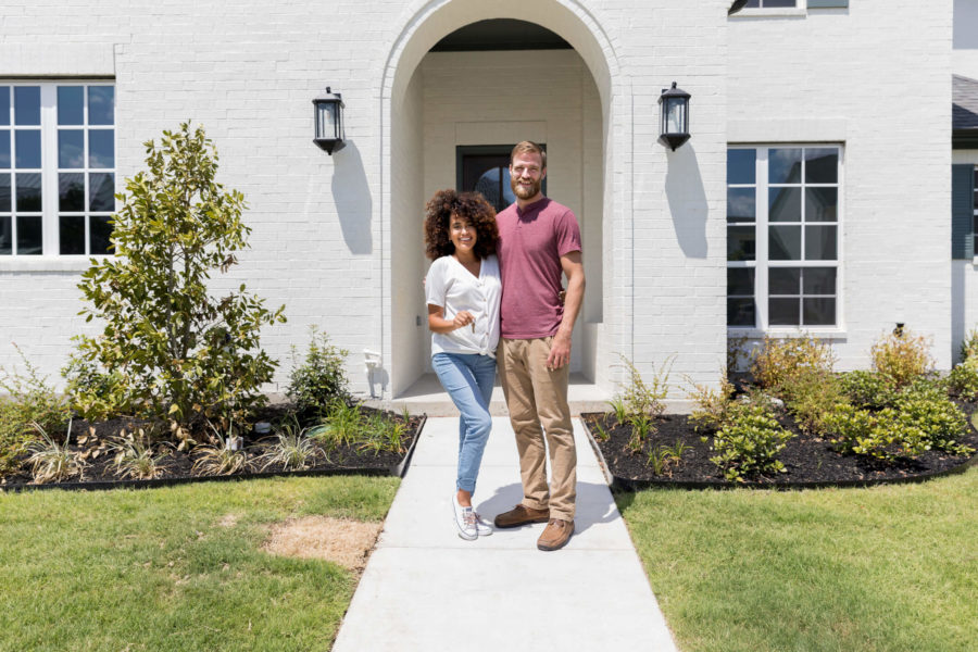 Happy expectant couple outside their new home