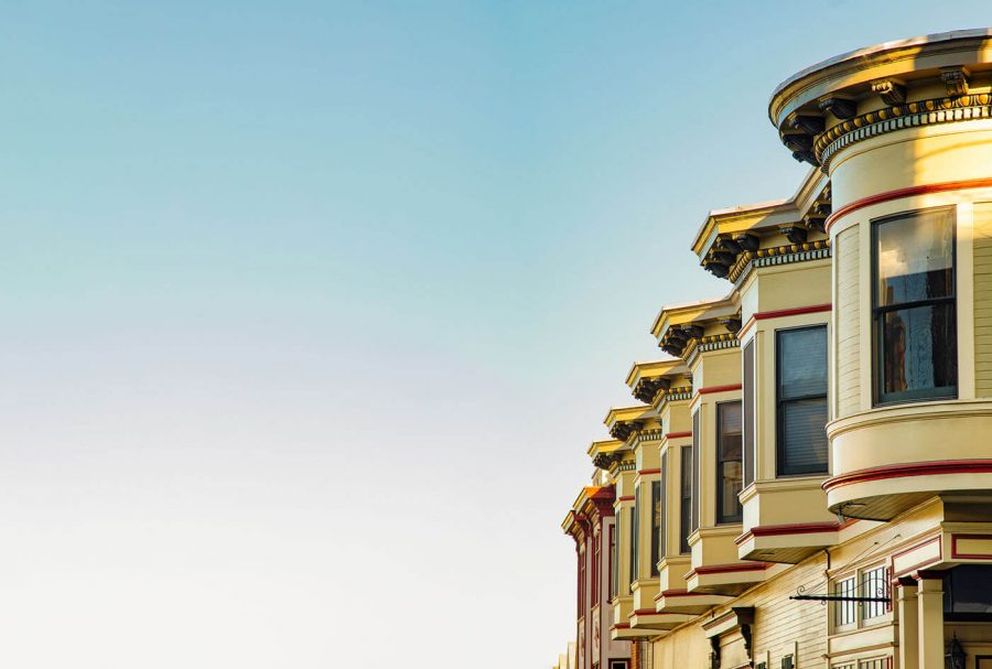 San Francisco residential house architecture with clear blue sky, featuring the upper floors of a row of Victorian houses