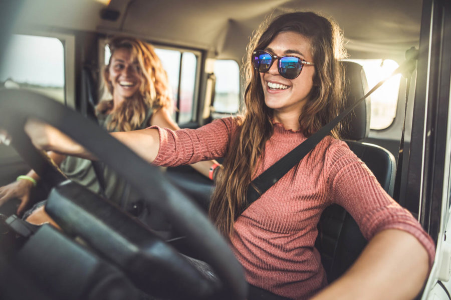 Happy female friends going on a road trip by car.