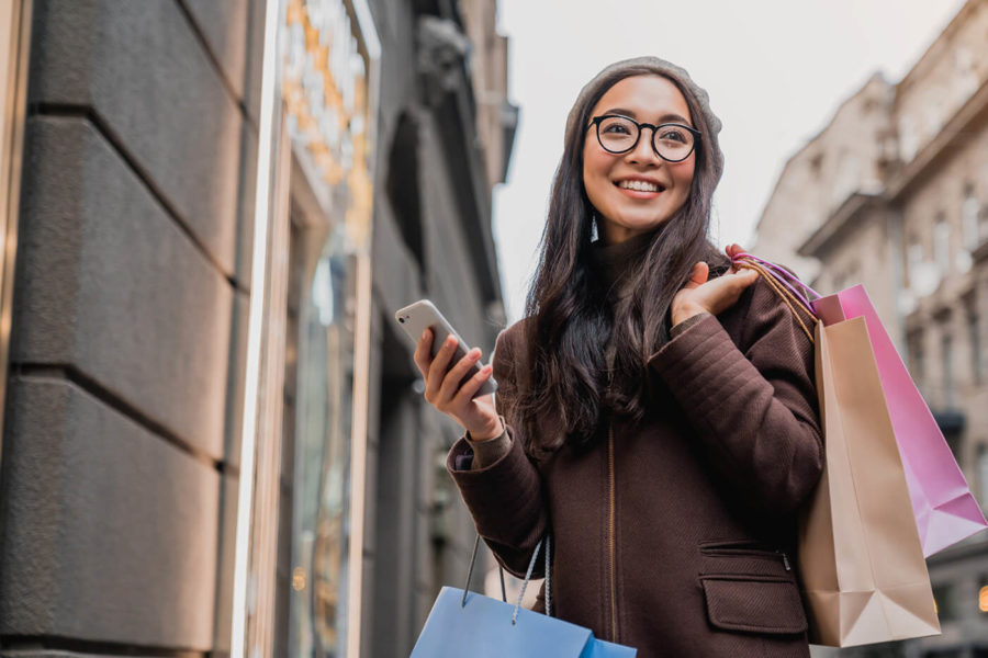 Asian woman using smartphone and looking away while enjoying a day shopping
