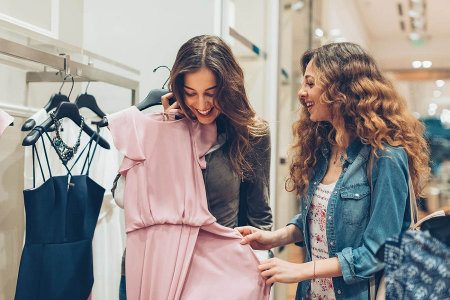 Two young women choosing dresses in a luxury fashion store