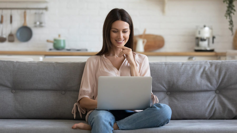 Smiling young woman using laptop, sitting on couch at home