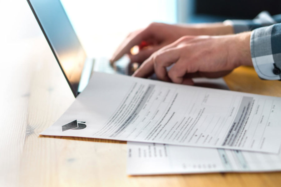 Young man writing college or university application form with laptop. Student applying to school. Scholarship document, admission paper or letter on table. Typing email.