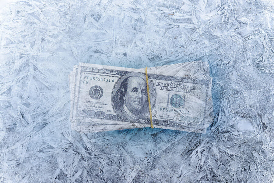 mixed image of frozen dollars in ice cube, global economic crisis and downsizing concepts