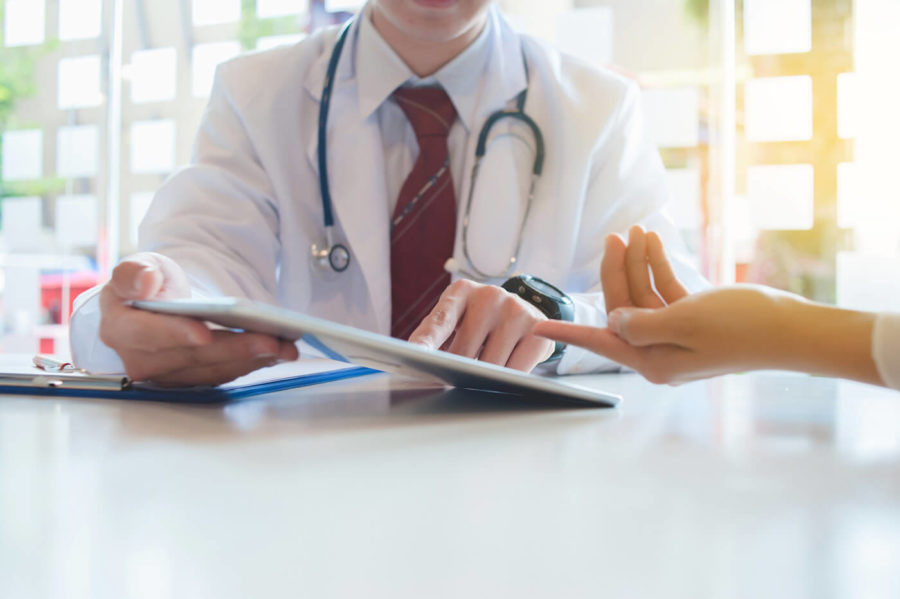 Doctor is consulting the patient with a digital tablet healthcare and technology concept