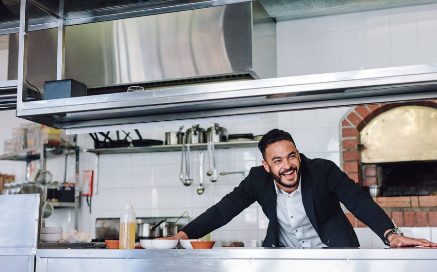 Smiling restaurant owner standing at kitchen counter