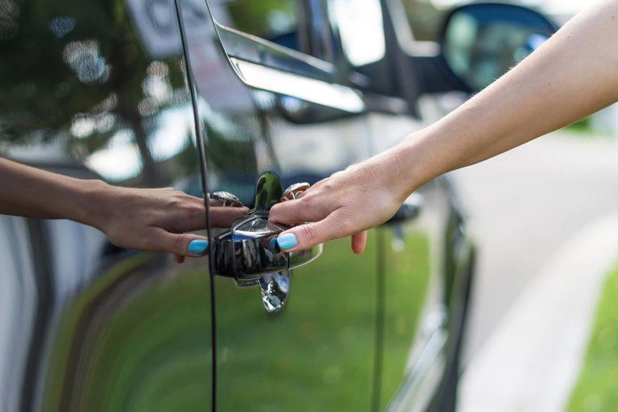 Female hand opening a car door
