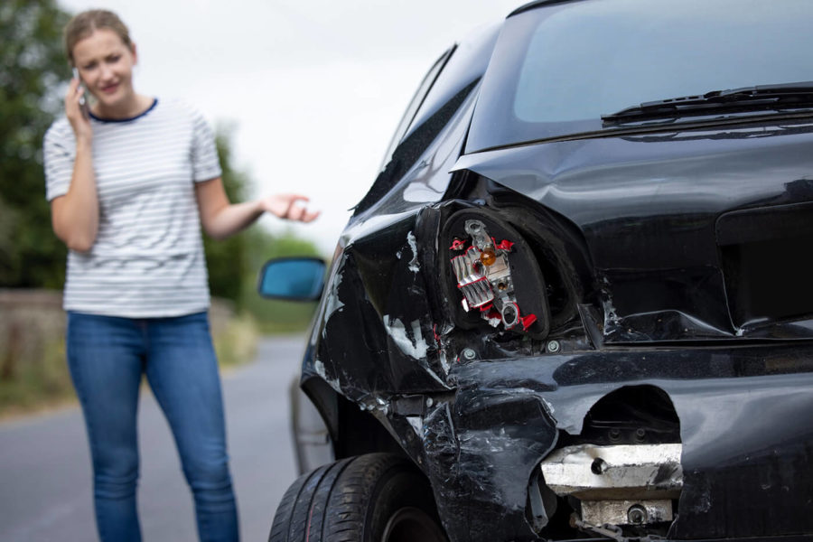 Unhappy Female Driver With Damaged Car After Accident Calling Insurance Company On Mobile Phone