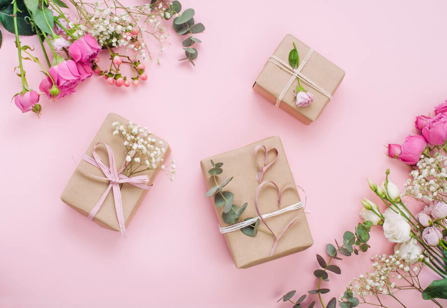 Craft paper wrapping gift boxes on pink background