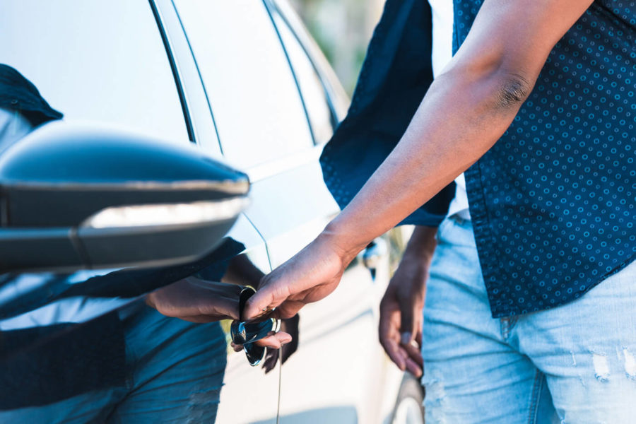 Unrecognizable man reaches for car door handle with left hand