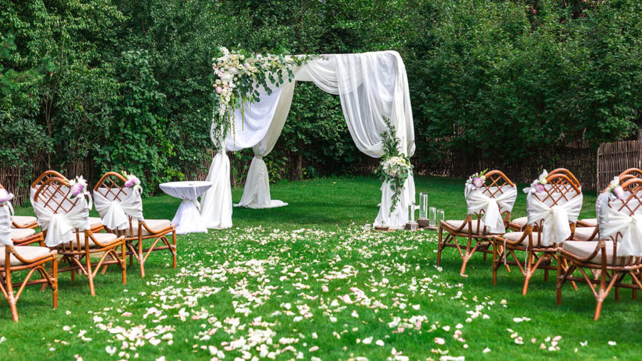 Beautiful setting for outdoors wedding ceremony waiting for bride and groom and guests. Decoration