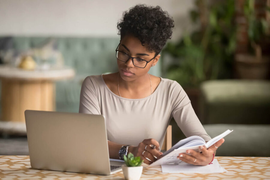 Focused African American student looking at laptop holding book doing research