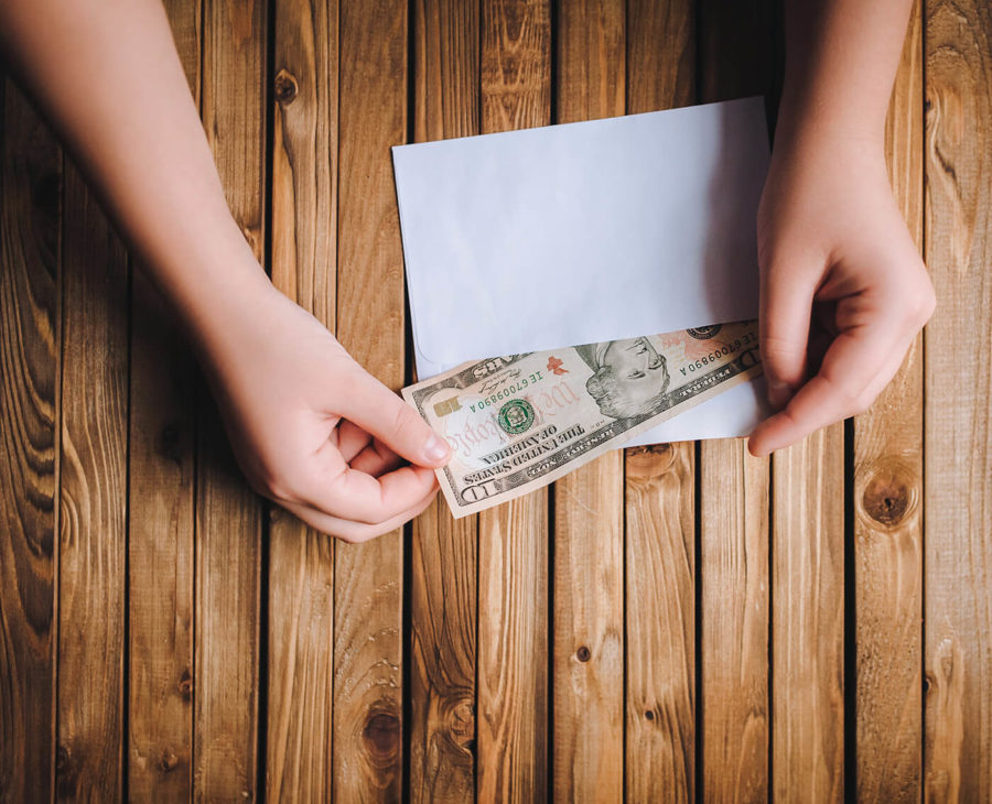 Dollars are taken out of the envelope or put in an envelope. Donation concept.