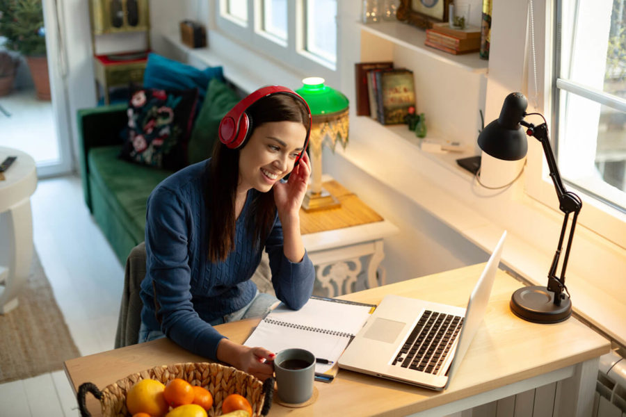 Attractive young woman teacher, teaching by holding an online class with her students from home using her laptop. Having a headphones on and smiling. Relaxed atmosphere and cozy ambient for the improvement of productivity.
