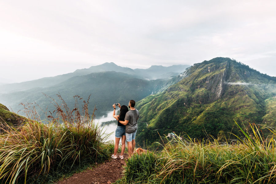 The couple travels the world. A couple in love travels to Sri Lanka. The couple travels to Asia. Man and woman meet the dawn in the mountains. Vacation in Asia. Happy couple in the mountains.