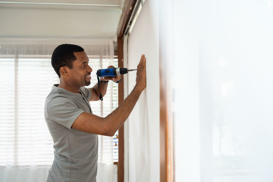 Smiling African American male using electric drill on the wall
