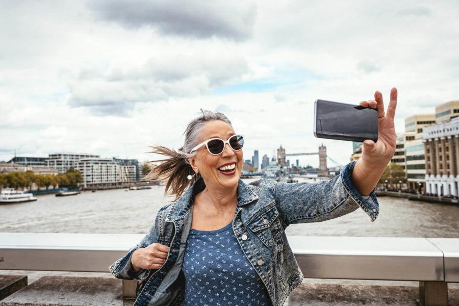Senior tourist in London taking selfie with Tower Bridge in background -