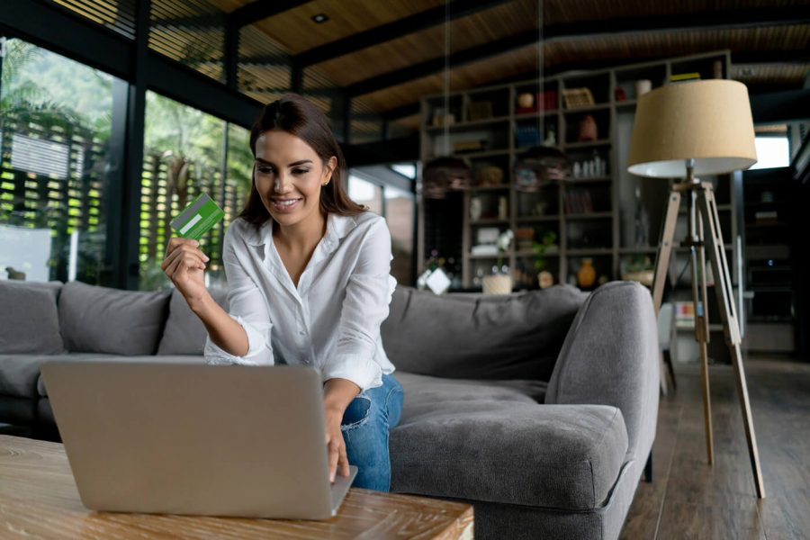 Cheerful latin american woman relaxing at home on a shopping spree online holding her credit card very happy