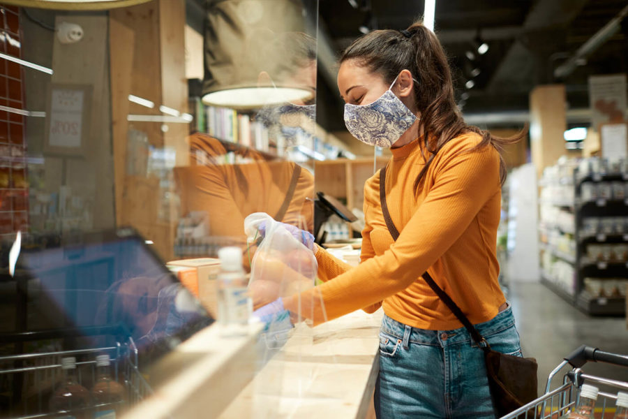 One woman at the supermarket check out and wearing a protective mask.