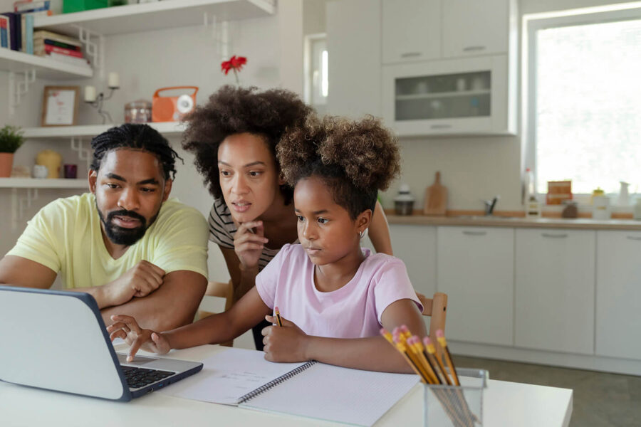 African American Parents Helping Their Daughter With Homework