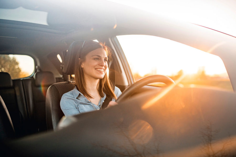 Young woman driving car on a sunny day