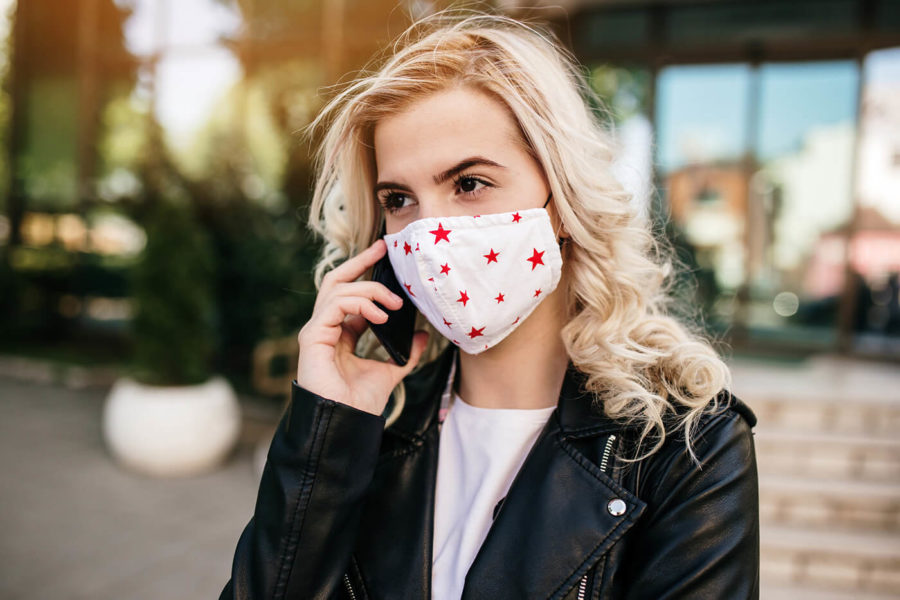 Woman with protective mask on city