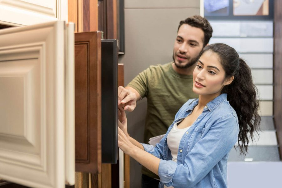 Couple look at cabinet samples in hardware store