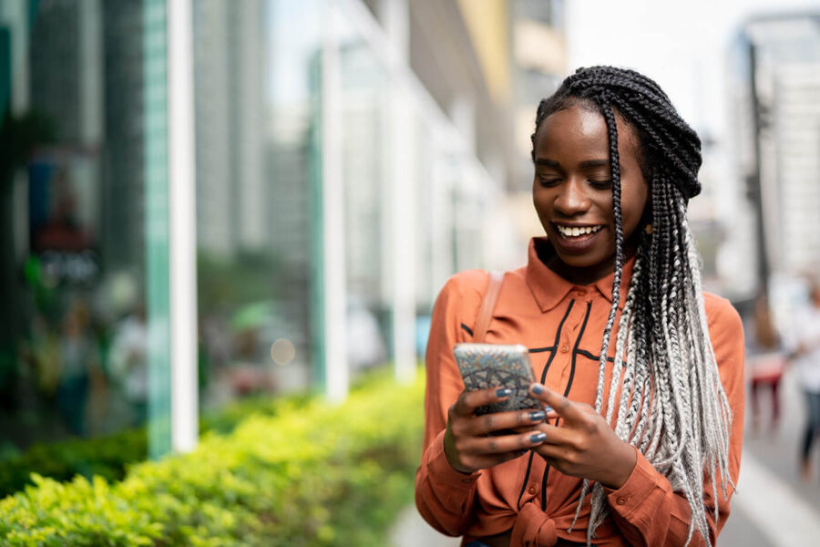 Afro Woman Using Mobile at Street