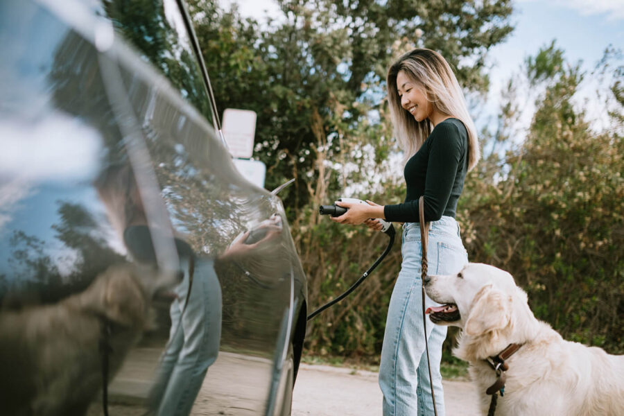 Woman With Dog Plugs In Electric Vehicle to Charge
