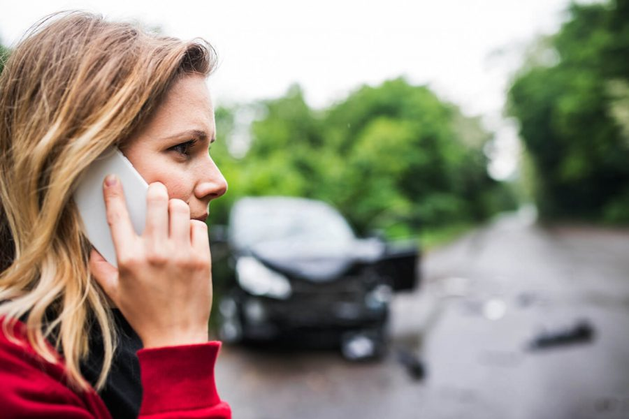 A young woman on the phone standing by the damaged car after a car accident.