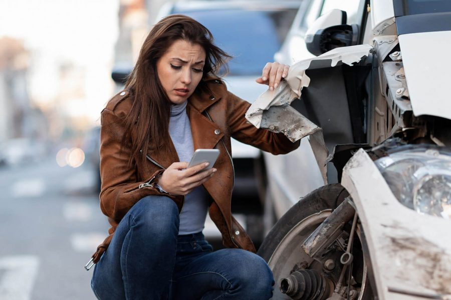 Displeased woman dialing for help after a car accident in the city.