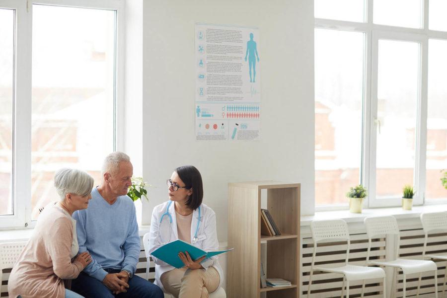 Female Doctor Registering Senior Couple Senior Couple